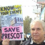 "Councillor Ian Smith holds up a sign says ""Know(sley) Your Enemy: Save Prescot."""